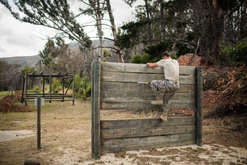 Soldat, der hölzerne Wand im Ausbildungslager klettert lizenzfreies stockfoto