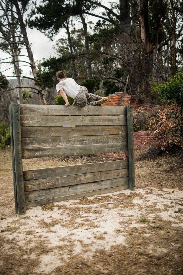 Soldat, der hölzerne Wand im Ausbildungslager klettert lizenzfreie stockfotografie