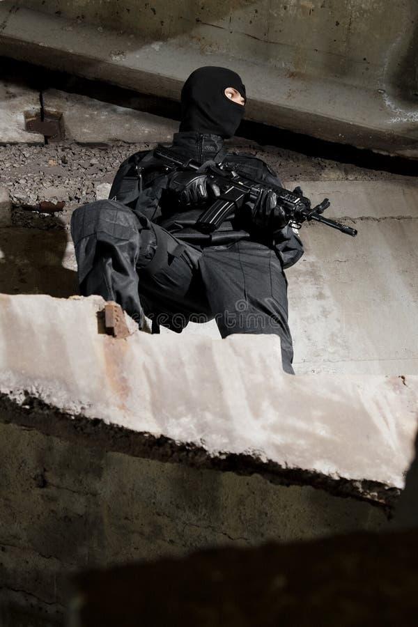 Soldat in der schwarzen Uniform mit Gewehr stockfoto