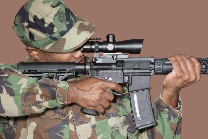 Soldat des USA Marine Corps de mâle visant le fusil d'assaut M4 au-dessus du fond brun photo stock