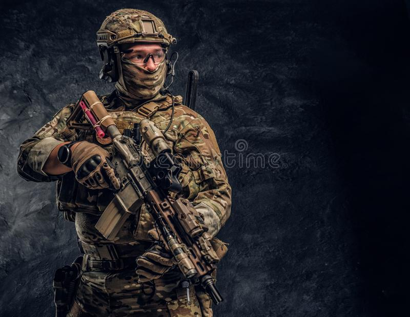 Soldat entièrement équipé dans l'uniforme de camouflage tenant un fusil d'assaut r photo libre de droits