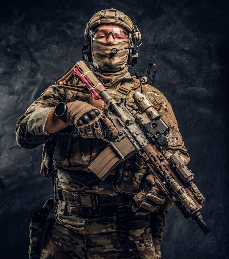 Soldat entièrement équipé dans l'uniforme de camouflage tenant un fusil d'assaut r image libre de droits