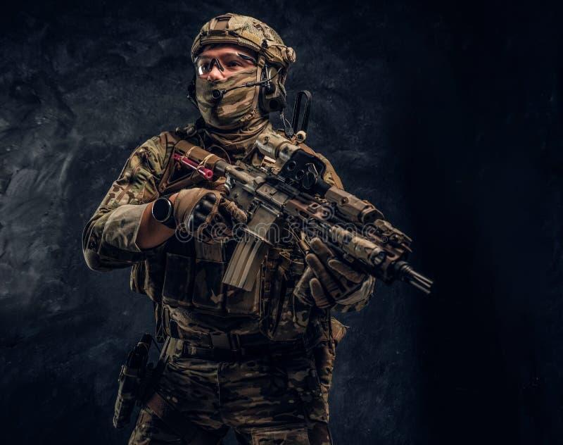 Soldat entièrement équipé dans l'uniforme de camouflage tenant un fusil d'assaut r photographie stock libre de droits