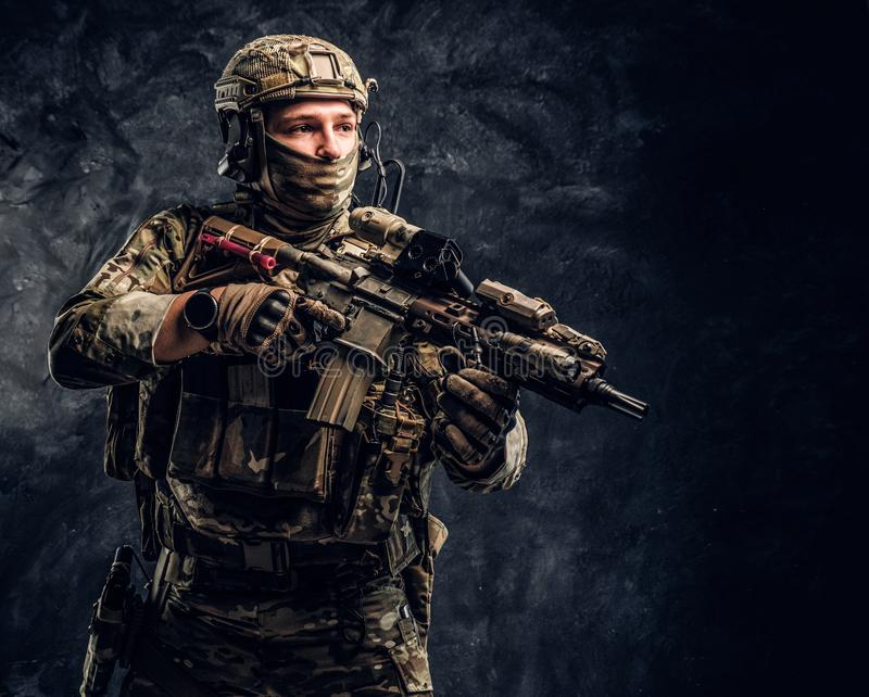 Soldat entièrement équipé dans l'uniforme de camouflage tenant un fusil d'assaut r photos stock