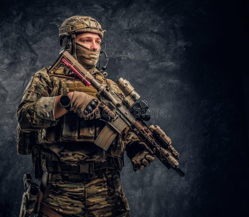 Soldat entièrement équipé dans l'uniforme de camouflage tenant un fusil d'assaut r photos libres de droits