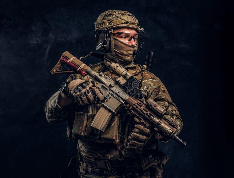 Soldat entièrement équipé dans l'uniforme de camouflage tenant un fusil d'assaut r photo stock
