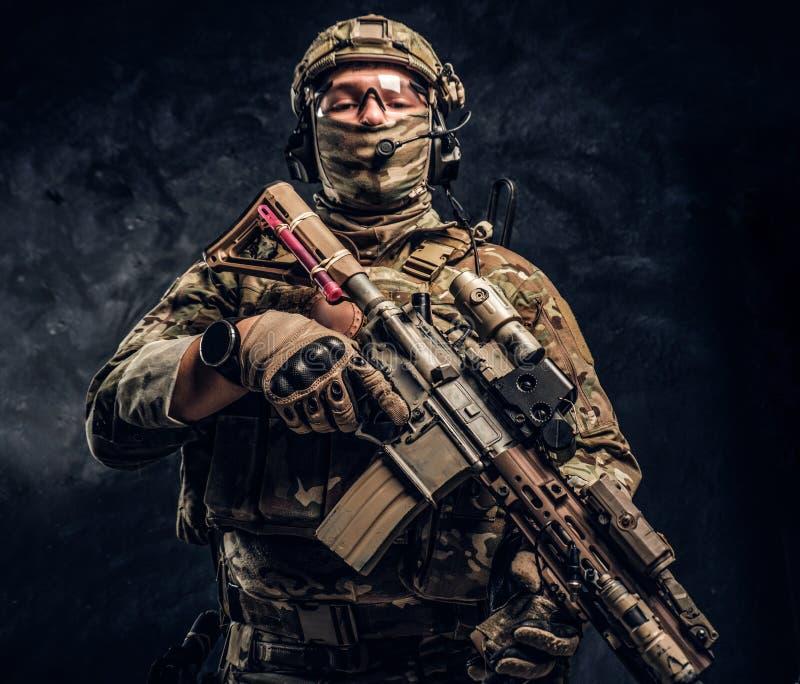 Soldat entièrement équipé dans l'uniforme de camouflage tenant un fusil d'assaut r images libres de droits