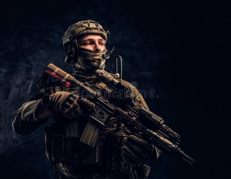 Soldat enti?rement ?quip? dans l'uniforme de camouflage tenant un fusil d'assaut r image libre de droits