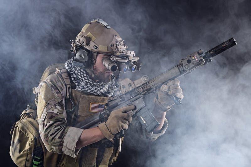 Soldat för USA-armé i handling med skyddsglasögon i röken fotografering för bildbyråer
