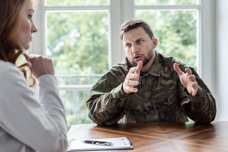 Soldat fatigué avec le syndrome de guerre parlant avec le thérapeute au cours de la réunion dans le bureau images libres de droits