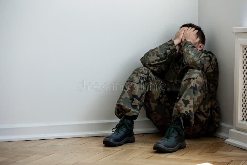 Soldat fatigué et déprimé avec seul le syndrome de guerre à la maison Copiez l'espace sur le mur photos libres de droits