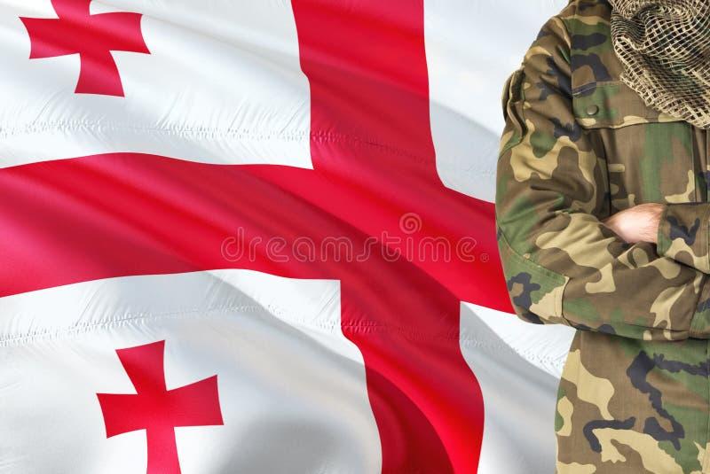 Soldat géorgien croisé de bras avec le drapeau de ondulation national sur le fond - thème de Georgia Military photographie stock