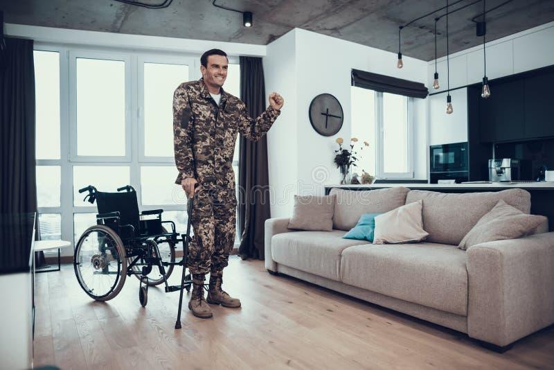 Soldat handicapé Leans sur la béquille près du fauteuil roulant photographie stock