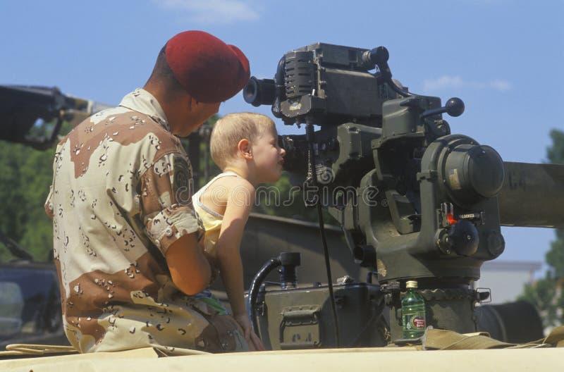 Soldat Holding Boy Looking på det militära vapnet, Washington, D C arkivbild