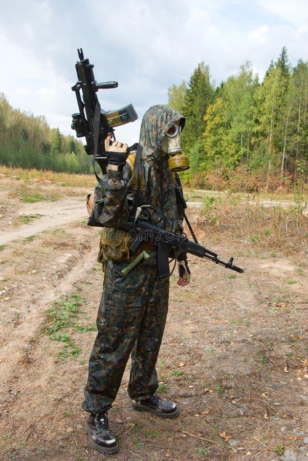 Soldat i gasmask med det automatiska vapnet fotografering för bildbyråer