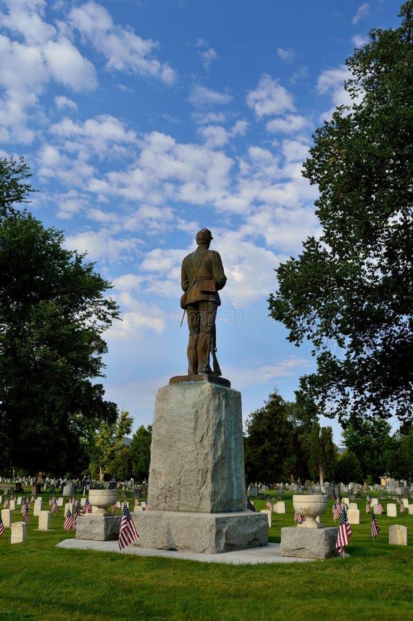 Soldat i himmel - staty i kyrkogård med minnes- veteransjälvständighetsdagenflaggor fotografering för bildbyråer