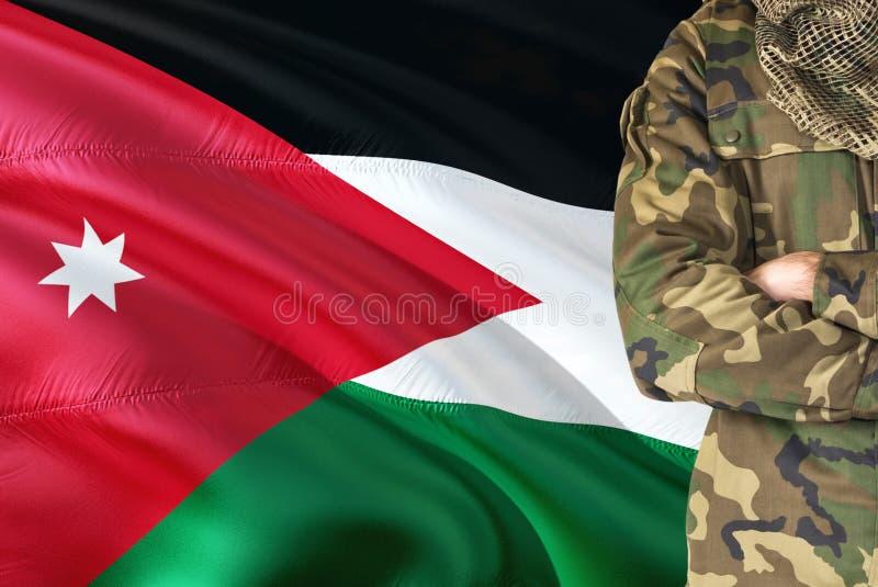 Soldat jordanien croisé de bras avec le drapeau de ondulation national sur le fond - thème de Jordan Military images stock