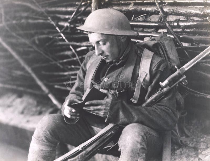 Soldat lisant un livre image stock