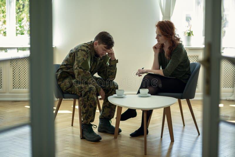 Soldat malheureux dans l'uniforme et le psychothérapeute verts pendant la consultation dans le bureau image libre de droits