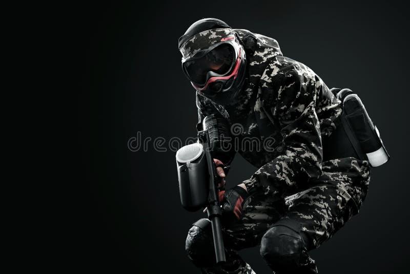 Soldat masqué fortement armé de paintball d'isolement sur le fond noir Concept d'annonce photos stock
