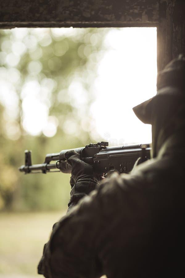 Soldat mettant le feu à l'arme automatique photographie stock
