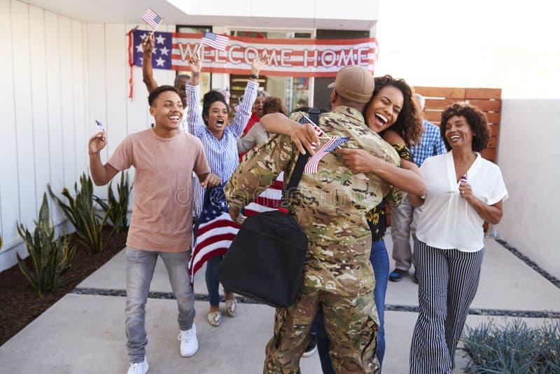 Soldat millénaire de embrassement de trois générations de famille enthousiaste d'Afro-américain leur retournant à la maison photos libres de droits