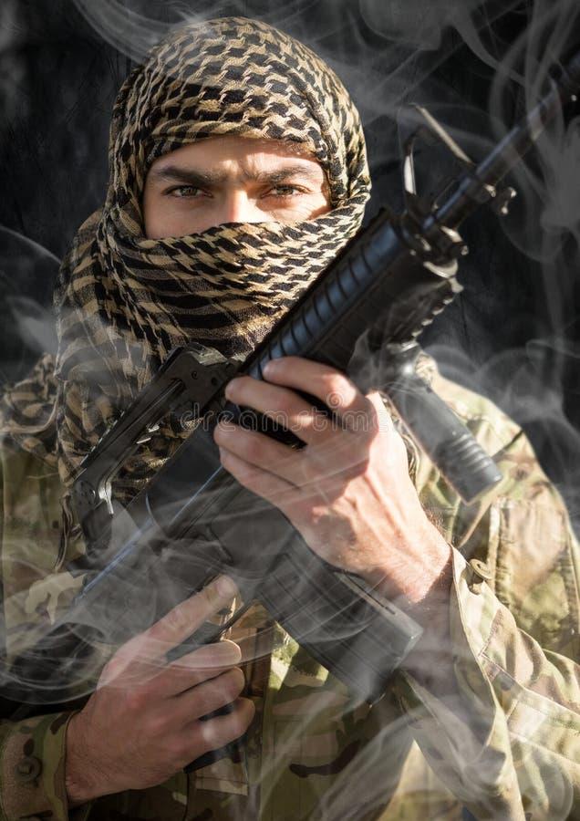 Soldat mit dem Gesicht bedeckt und Waffe in seinen Händen, uns schauend Rauch um ihn Schwarzer Hintergrund lizenzfreie stockfotografie