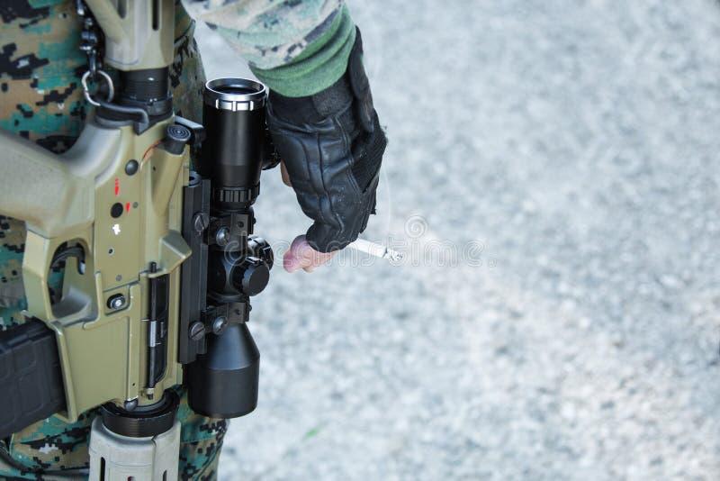 Soldat mit Gewehren und der Zigarette stockfotos