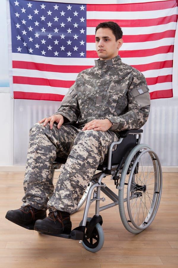 Soldat patriote s'asseyant sur le fauteuil roulant contre le drapeau américain image libre de droits
