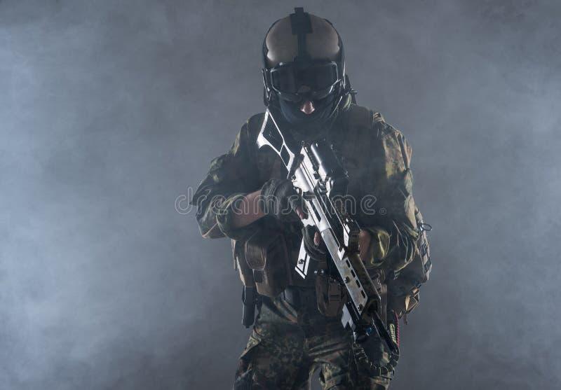 Soldat sérieux tenant le fusil d'assaut dans des mains photos libres de droits