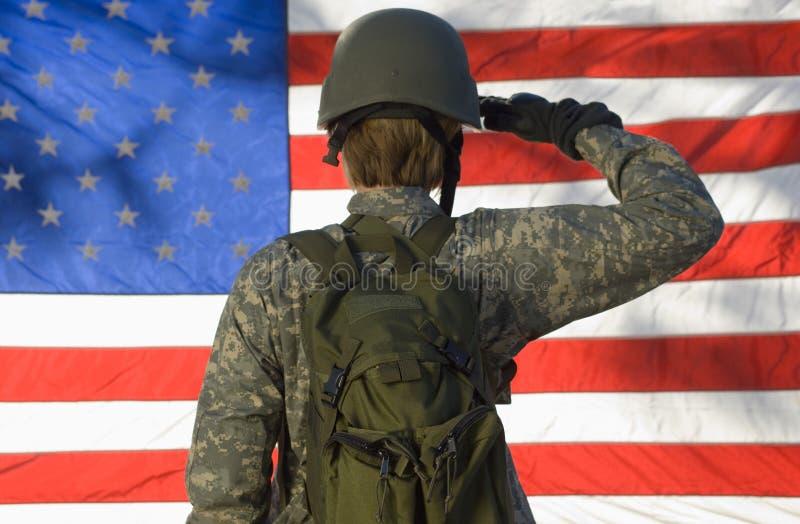 Soldat Saluting In Front Of American Flag stockbild
