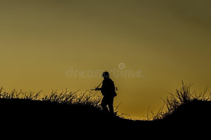 Soldat solitaire avec un fusil, sur une colline photo libre de droits