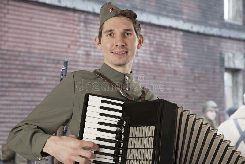 Soldat soviétique jouant l'accordéon dehors photographie stock