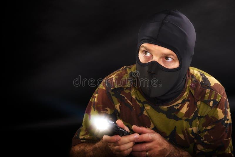 Soldat sur un fond noir avec une lampe-torche photos stock