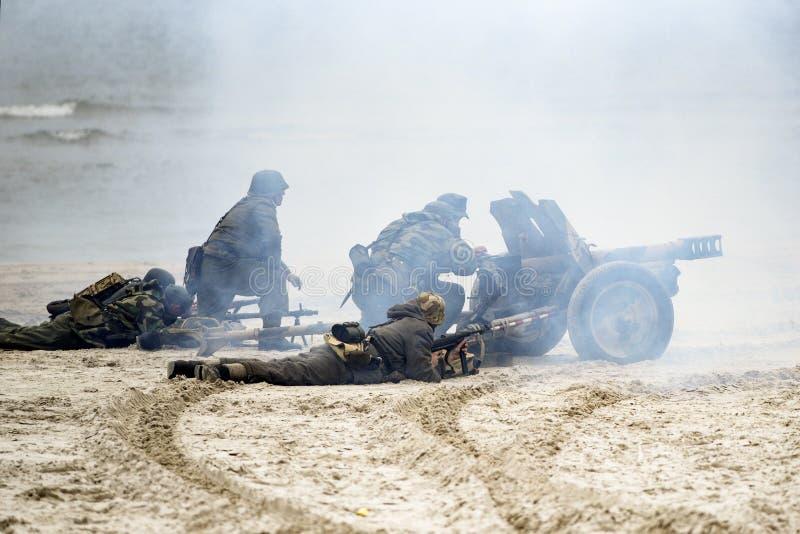 Soldaten, die auf dem Strand während der Rekonstruktion des historischen Kampfes mit WWII kämpfen lizenzfreies stockfoto