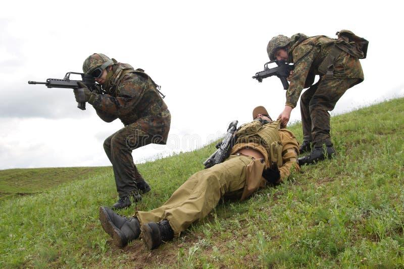 Soldaten, die ihren verletzten Partner sichern stockbild