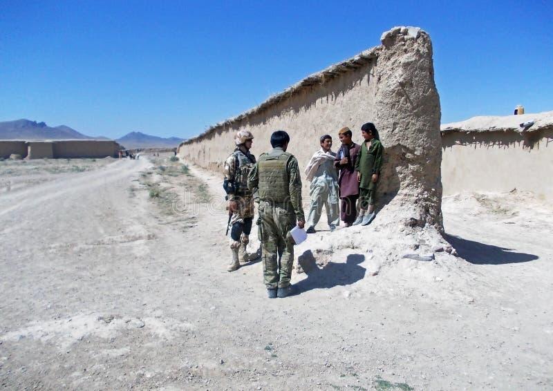 Soldaten, die mit einigen Kindern in Afghanistan sprechen stockfotos