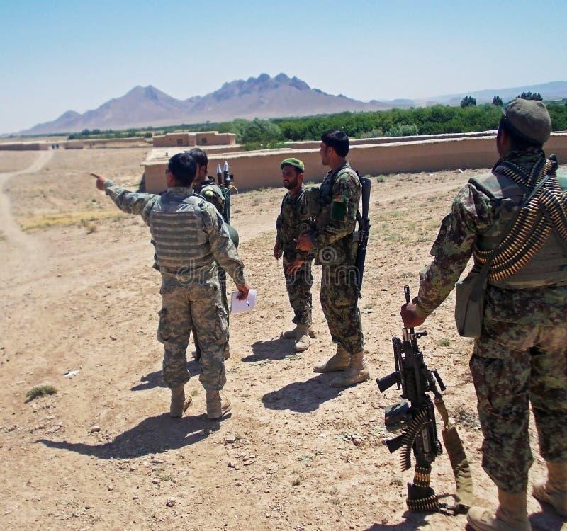 Soldaten, die nach Richtungen in ein Dorf in Afghanistan suchen stockfotografie