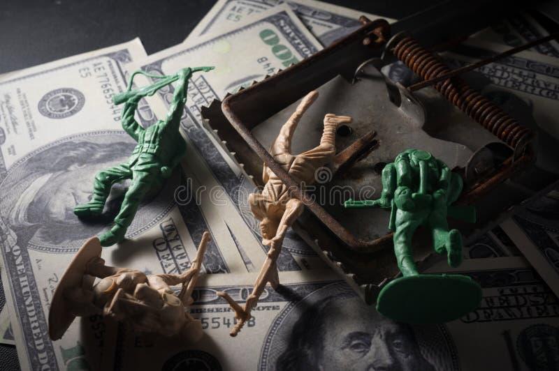 Soldaten leker med musfälla på pengar arkivbilder
