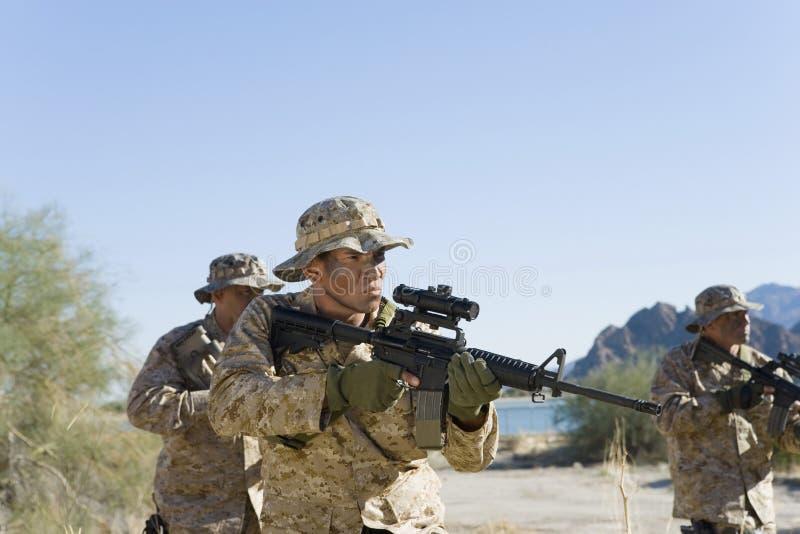 Soldaten mit Gewehren in The Field lizenzfreies stockfoto