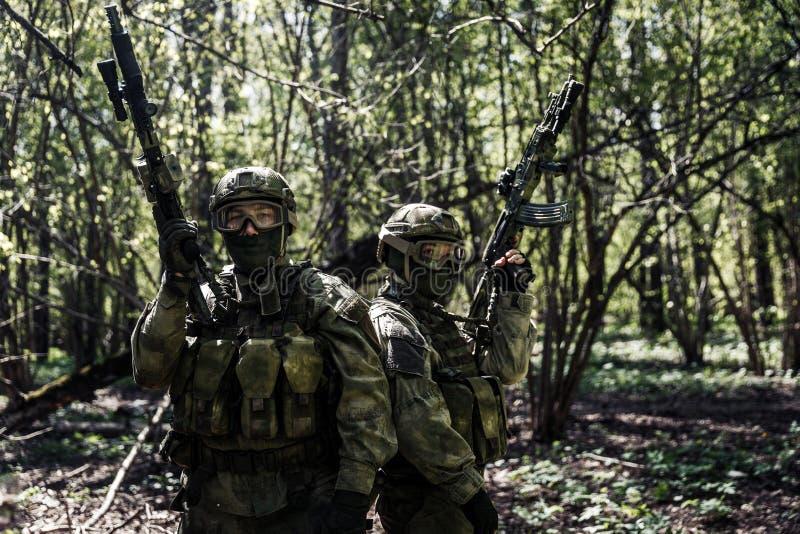 Soldaten mit Waffen im Wald lizenzfreie stockfotos
