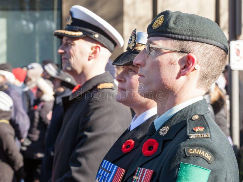Soldater från den kanadensiska armén, två män, en kvinna, från marinen & marktrupper, bärande minnevallmo som står på ceremoni royaltyfri bild