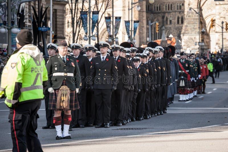 Soldater fr?n den kanadensiska arm?n, m?n och kvinnor fr?n den kungliga b?rande minnevallmo f?r kanadensisk marin som st?r p? cer royaltyfria foton