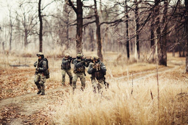 Soldater med vapen på fältet arkivbilder