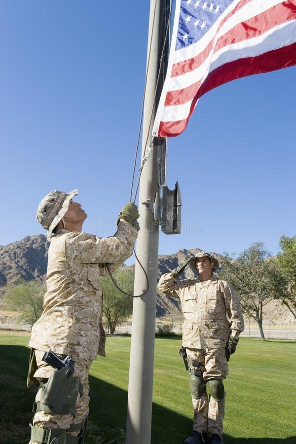Soldater som lyfter Förenta staternaflaggan arkivfoton