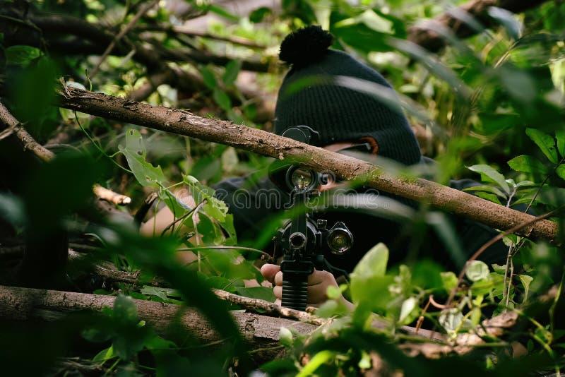 Soldater som siktar målet, och innehav som hans dolde gevär överfalla från bakhåll, arméprickskyttkamouflage i skog royaltyfria foton