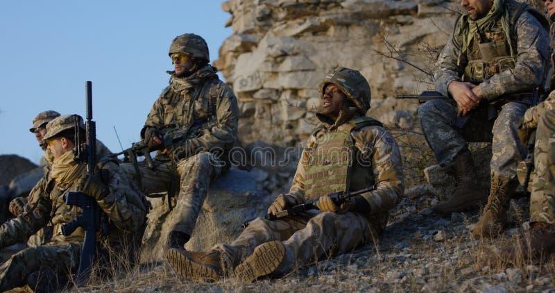 Soldater som sitter under ett avbrott i en anfall fotografering för bildbyråer