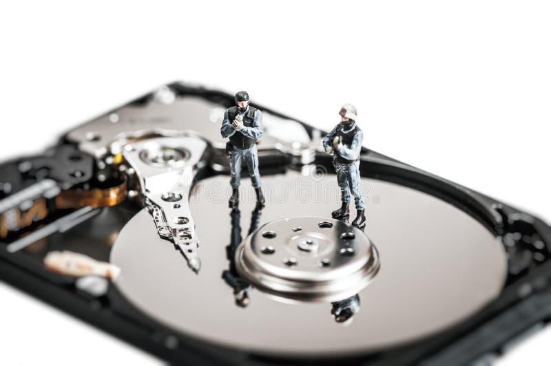 Soldati miniatura che proteggono il disco rigido del computer Concetto di tecnologia immagini stock