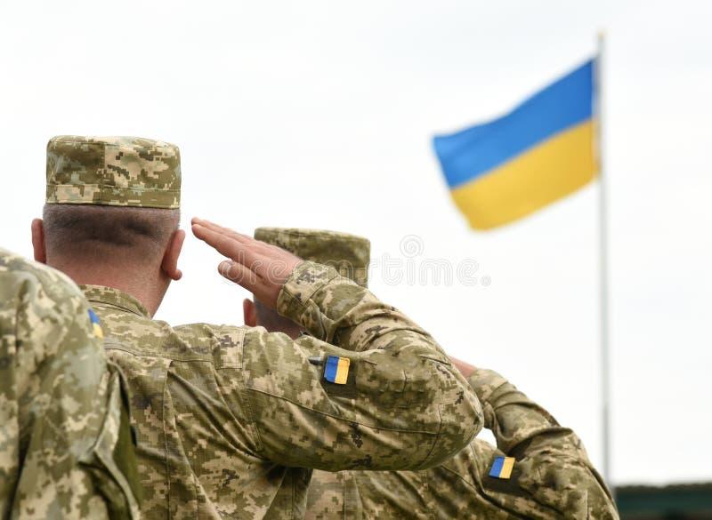 Soldati ucraini che danno saluto Bandierina dell'Ucraina fotografia stock