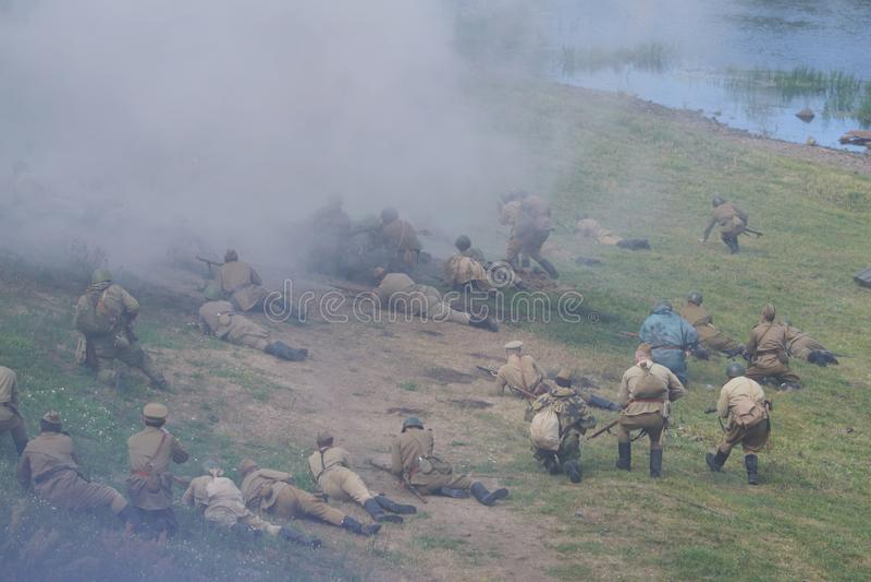 Soldati in uniformi sovietiche, con i fucili di assalto, bugia sulla terra sulla sponda del fiume, nel fumo fotografia stock libera da diritti